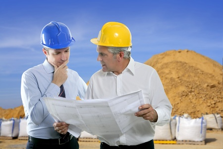 sand quarry: architect engineer two expertise team plan talking hardhat quarry sand sacks blue sky