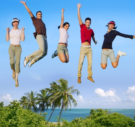 Jumping young people happy group vacation tropical beach photo