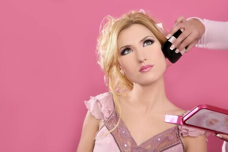 Makeup artist hand working on beautiful blonde face pink background Stock Photo - 8621572