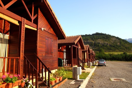 Wooden bungalow row in camping camp park in mountains