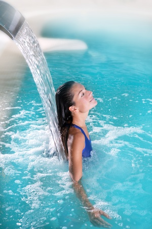 spa hydrotherapy woman waterfall jet turquoise swimming pool water photo