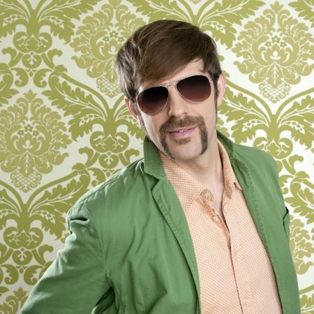friki: Geek vendedor retro hombre divertido bigote gafas en papel tapiz verde Foto de archivo