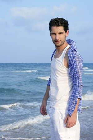 Mediterranean latin young man on summer blue beach wakling relaxed photo