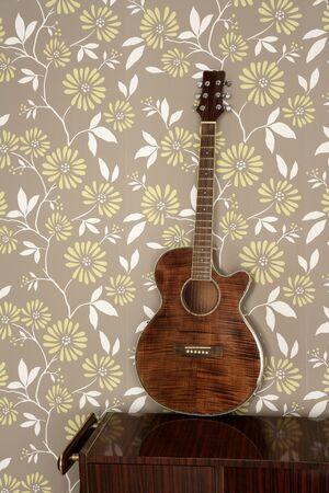 acoustic guitar retro on vintage 60s wallpaper wooden furniture photo