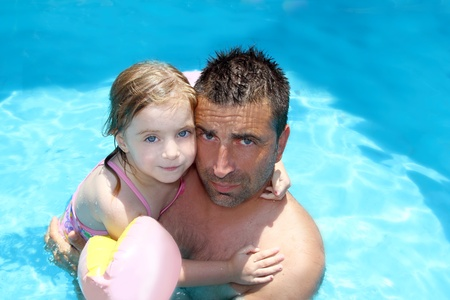 father daughter hug on blue swimming pool vacation portrait photo