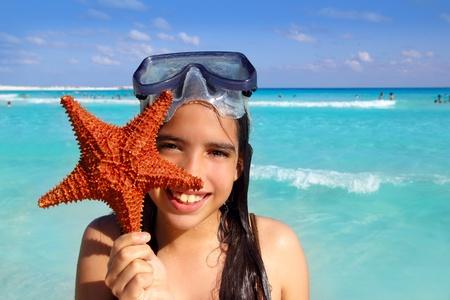 latin tourist girl holding starfish in tropical beach Stock Photo