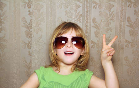 hand victory gesture little girl funny sunglasses retro wallpaper Stock Photo - 9030769