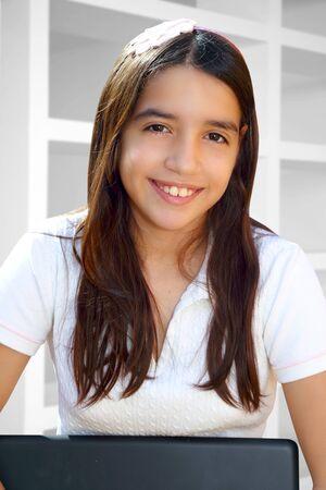 hispanic student: Estudiante adolescente Latina sonriente port�til de explotaci�n casa blanca interior Foto de archivo