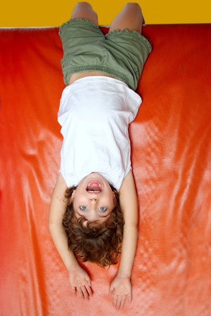upside down little girl on playground slide laughing happy play Stock Photo - 9030946