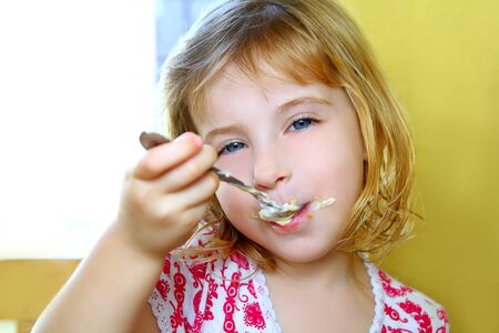 hungry little blond girl spoon eating ice cream pastry dirty mouth photo
