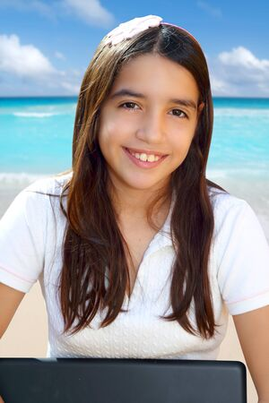 Latin teenager student smiling holding laptop in beach photo