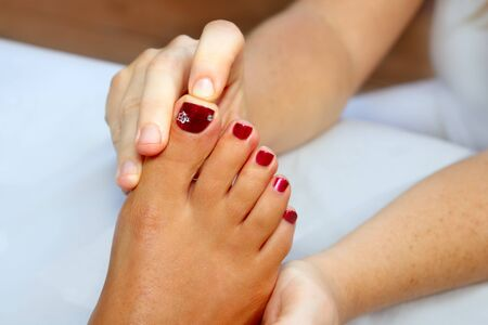 soothe: Reflexology woman feet massage therapy outdoor Stock Photo