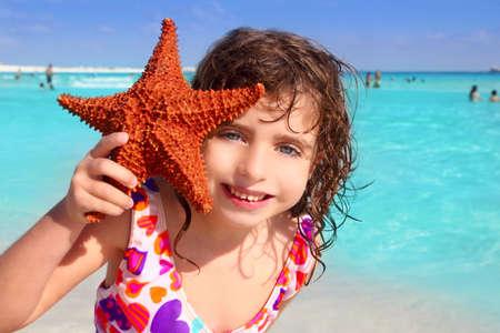 little beautiful  tourist girl holding starfish tropical beach photo