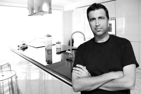 Medium age man in modern kitchen interior portrait crossed arms photo