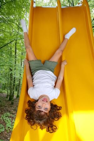 Brunette little girl upside down playground slide forest tree park Stock Photo - 9142738