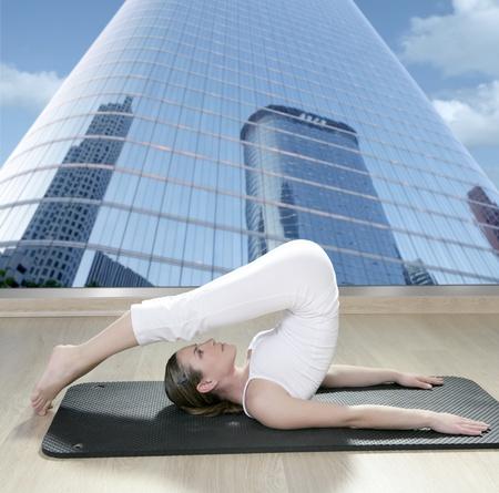 black mat yoga woman window view of city urban buildings photo