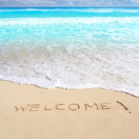 welcome: greetings welcome beach spell written on sand Caribbean tropical sea Stock Photo