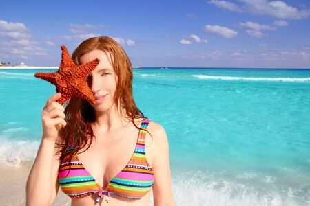 bikini tourist redhead woman holding starfish tropical beach photo