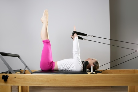 gym woman pilates stretching sport in reformer bed instructor girl photo