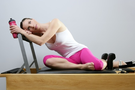 aerobic gym pilates woman rest holding water bottle in reformer bed photo