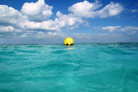 Buoy yellow floating in tropical Caribbean sea blue sky photo