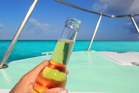 caribbean drink: beer on hand Caribbean in boat bow turquoise sea enjoying vacation