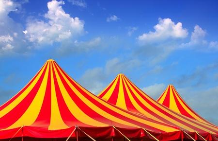 서커스 텐트 빨간색 오렌지와 노란색 박탈 패턴 푸른 하늘