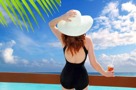 beach hat rear view woman cocktail tropical beach black swimsuit photo