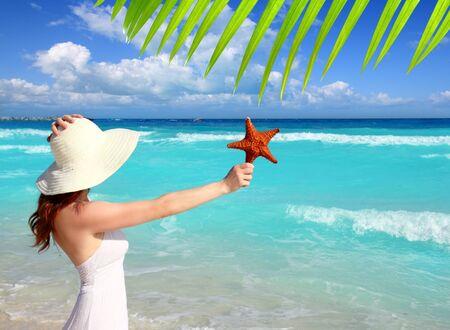 beach hat woman starfish in hand tropical turquoise Caribbean photo