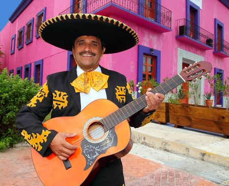 mariachi: Charro Mariachi singer playing guitar in Mexico houses background Stock Photo