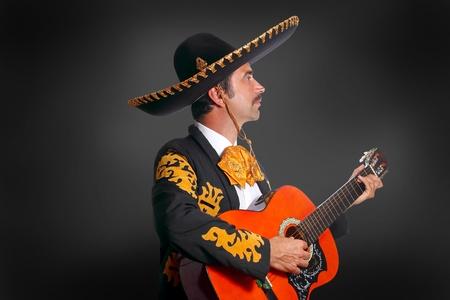 traje mexicano: Charro Mariachi tocando la guitarra en fondo negro