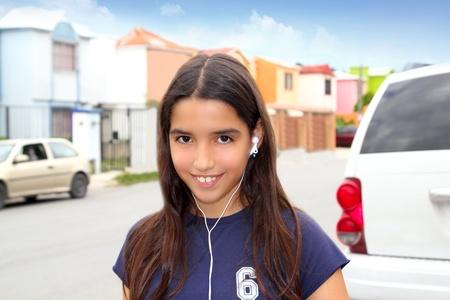 hispanic latin teenager girl earphones hearing music smiling in street photo