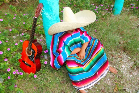 Mexican lazy sombrero hat man poncho nap in garden typical topic photo