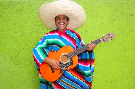 Mexican typical man playing guitar poncho on green wall photo