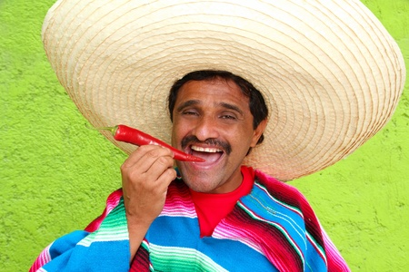 Mexican man poncho sombrero eating red chili hot pepper Mexico photo