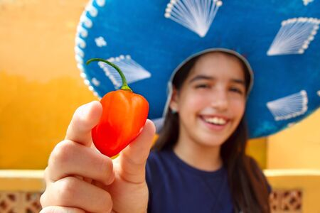 Mexican girl show habanero orange hot chili pepper mexican hat photo