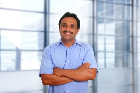 gentile: Indian latin businessman blue shirt in modern office background Stock Photo