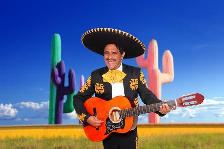 traje mexicano: Canto de charro mariachi mexicano tocando la guitarra en fondo de cactus México