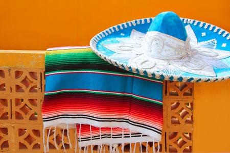 trajes mexicanos: poncho de serape de charro mariachi azul sombrero mexicano sobre el muro de Tejas naranja