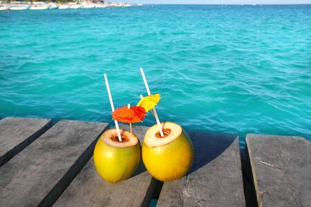 coconut coktails in caribbean on wood pier turquoise sea photo