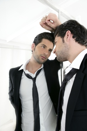 enticement: Handsome narcissistic suit proud young man looking himself in the mirror