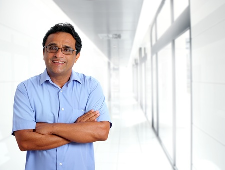 indian latin businessman glasses blue shirt in modern office corridor photo
