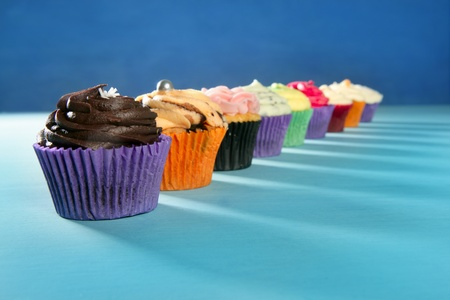 Cupcakes colorful cream muffin arrangement in a row line on turquoise photo