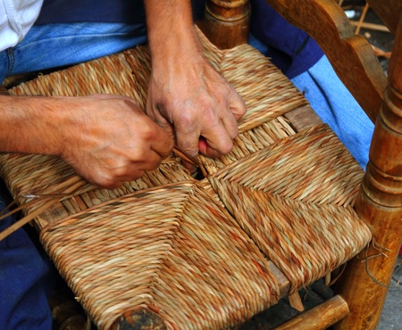 enea traditional spain dried reed chair handcraft man hands working seat photo