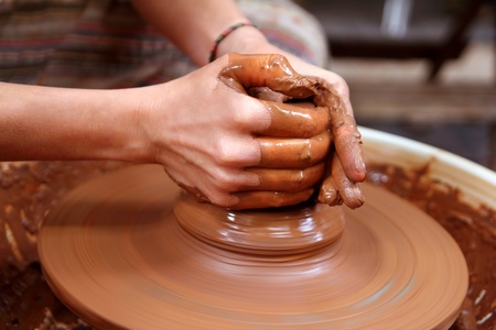 sculptor: clay potter hands closeup working on wheel handcrafts pottery work