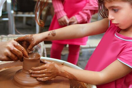 sculptor: clay potter hands wheel pottery work workshop teacher and girl pupil Stock Photo