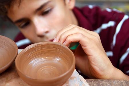 ollas barro: Bol de arcilla de potter adolescente chico trabajando en las artes tradicionales de taller de cer�mica Foto de archivo