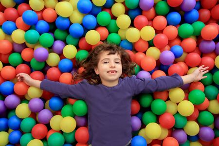 playcentre: colorful balls funny park little girl lying gesturing happy