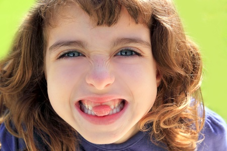 indented little girl sticking tongue between teeth smiling portrait photo