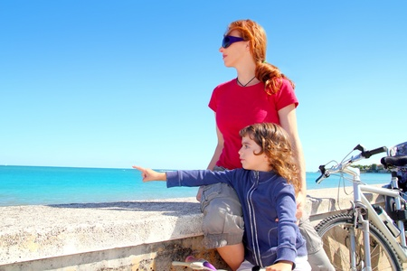 daughter and mother on bicycle in beach sea vacation pointing finger photo
